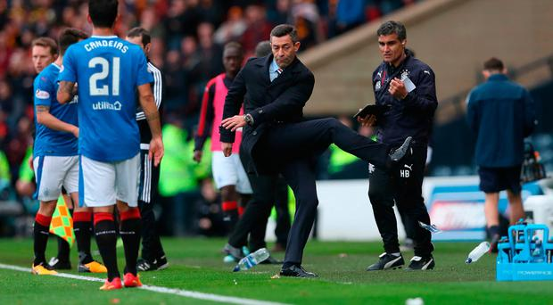 Angry: Rangers boss Pedro Caixinha kicks out at a water bottle