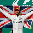 Flying the flag: Lewis Hamilton celebrates on the podium after his United States GP triumph