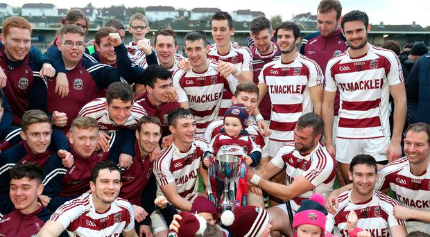 In the bag: Slaughtneil celebrate lifting the Ulster hurling title but their dual code stars go right back to work