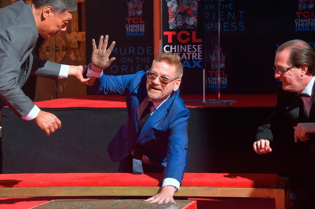 Actor Kenneth Branagh gestures while placing his hands into the block of cement at his Hand and Footprints Ceremony in front of the TCL Chinese Theater in Hollywood, California on October 26, 2017, where he was joined by