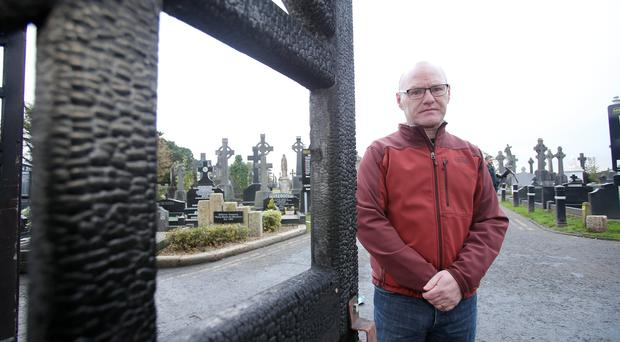 The scene at Milton Cemetery in west Belfast where a gang of youths set the gates on fire on Friday night. Sinn Fein MP for the area Paul Maskey pictured at the scene.