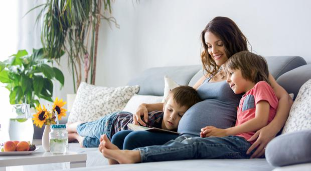 Scan dilemma: a pregnant mum reads with her sons