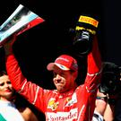 Home first: Race winner Sebastian Vettel celebrates on the podium after the Brazilian Grand Prix