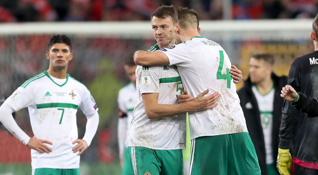 Brave effort: Jonny Evans and Gareth McAuley embrace after the draw in Basel, which wasn't enough to keep Northern Ireland's World Cup dream alive