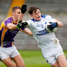 Man marked: Luke Fortune runs the ball out from his own goals as Conal Jones gives chase