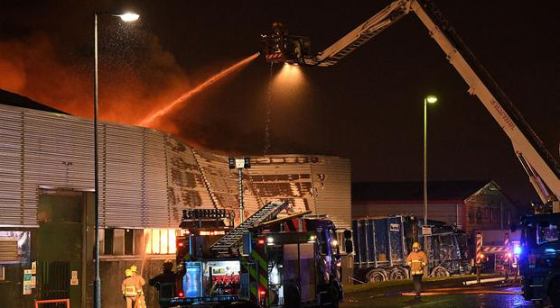 Firefighters and over ten fire appliances battling with a huge blaze at a warehouse in Mallusk, County Antrim this evening. / Credit: Alan Lewis/ Justin Kernoghan