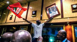 TOPSHOT - A man holds a Mozambican Liberation Movement (FRELIMO) flag and a poster with the portrait of former Zimbabwean deputy President Emmerson Mnangagwaafter removing the portrait of former Zimbabwean President Robert Mugabe from the wall at the International Conference centre, where parliament had their sitting, after his resignation on November 21, 2017 in Harare. Robert Mugabe resigned as president of Zimbabwe on November 21, 2017 swept from power as his 37-year reign of brutality and autocratic control crumbled within days of a military takeover. The bombshell news was delivered by the parliament speaker to a special joint session of the assembly which had convened to impeach Mugabe, 93, who has dominated every aspect of Zimbabwean public life since independence in 1980. / AFP PHOTO / Jekesai NJIKIZANAJEKESAI NJIKIZANA/AFP/Getty Images