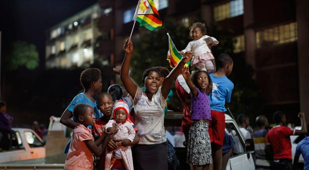 Zimbabweans celebrate at night at an intersection in downtown Harare, Zimbabwe Tuesday, Nov. 21, 2017. Pic: AP Photo/Ben Curtis