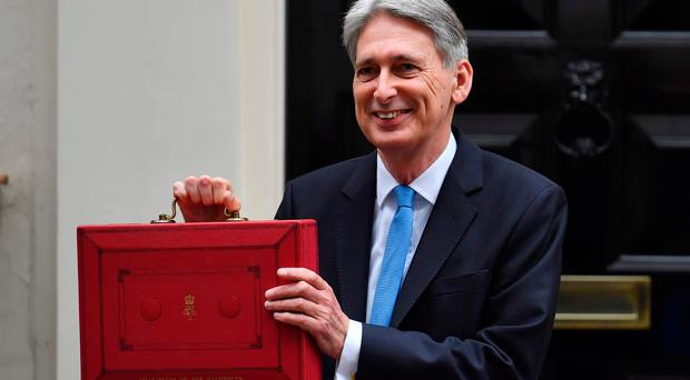 British Chancellor of the Exchequer Philip Hammond poses for pictures with the Budget Box as he leaves 11 Downing Street in London, on November 22, 2017, before presenting the government's annual Autumn budget to Parliament. Britain's Conservative government unveils its annual budget on November 22, against the backdrop of looming Brexit and sluggish economic growth. / AFP PHOTO / Ben STANSALLBEN STANSALL/AFP/Getty Images