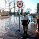 People make their way through flood water in Mountmellick, Co Laois, after three rivers burst their banks and flooded dozens of homes