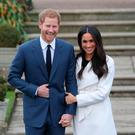 Britain's Prince Harry and his fiancée US actress Meghan Markle react as they pose for a photograph in the Sunken Garden at Kensington Palace AFP PHOTO / Daniel LEAL-OLIVASDANIEL LEAL-OLIVAS/AFP/Getty Images