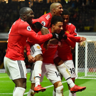 Gard of honour: Jesse Lingard is mobbed by United team-mates after his insurance goal at Watford last night