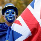 An anti-Brexit, pro European Union campaigner holds a Union flag, near Parliament in London. (AP Photo/Kirsty Wigglesworth)