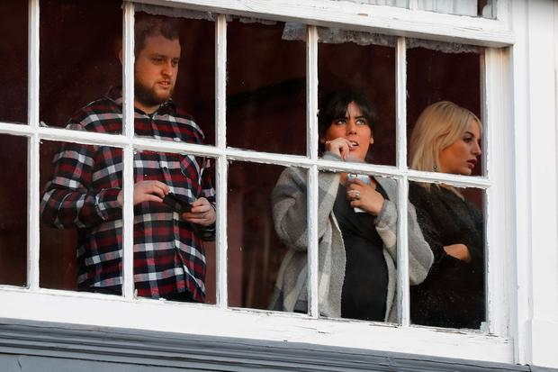 People look out from a window above Kringle's Toy Emporium as they wait to greet Prince Harry and his fiancee US actress Meghan Markle when they arrive for a walkabout and an engagement at the Nottingham Contemporary in Nottingham, central England, on December 1, 2017. Prince Harry and Meghan Markle visited Nottingham in their first set of engagements together since announcing their engagement. / AFP PHOTO / POOL / Adrian DENNISADRIAN DENNIS/AFP/Getty Images