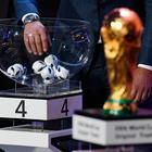 A draw assistant picks up a ball next to the official FIFA World Cup trophy during the 2018 FIFA World Cup football tournament final draw at the State Kremlin Palace in Moscow on December 1, 2017. The 2018 FIFA World Cup will be held between June 14 and July 15, 2018 in 11 Russian cities. / AFP PHOTO / Kirill KUDRYAVTSEVKIRILL KUDRYAVTSEV/AFP/Getty Images