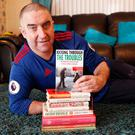 Brought to book: John White proudly shows off his book 'Kicking Through the Troubles'
