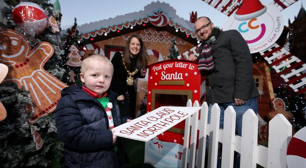 Toby (7) posts his letter to Santa, watched by his Dad Chris and Lord Mayor Cllr Nuala McAllister. Proceeds from Santa's grotto at the Christmas Market this year will go to the Children's Cancer Unit Charity. Mandatory Credit ©INPHO/Matt Mackey Presseye - Belfast - Northern Ireland