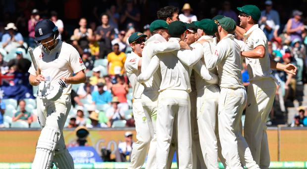 Aussie rules: Jonny Bairstow trudges off as Australian players celebrate after defeating England in the second Ashes Test in Adelaide