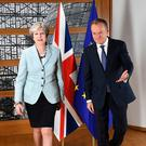 British Prime Minister Theresa May (L) and European Council President Donald Tusk leave after posing for photographers at the European Council in Brussels on December 8, 2017.