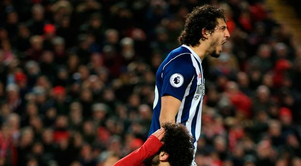 Up and down: Ahmed Hegazi roars at his fellow defender as Mohamed Salah reacts to a missed opportunity