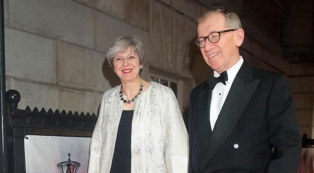 Theresa May and her husband Philip arrive at a function in London's Banqueting House last night. Left, the PM in the Commons earlier in the day