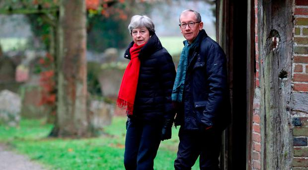 Theresa May and her husband Philip on their way to church yesterday