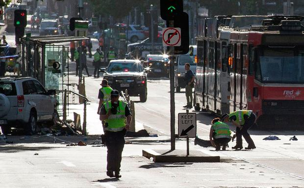 A white SUV (far L) sits in the middle of the road as police and emergency personnel work at the scene of where a car ran over pedestrians in Flinders Street in Melbourne on December 21, 2017.