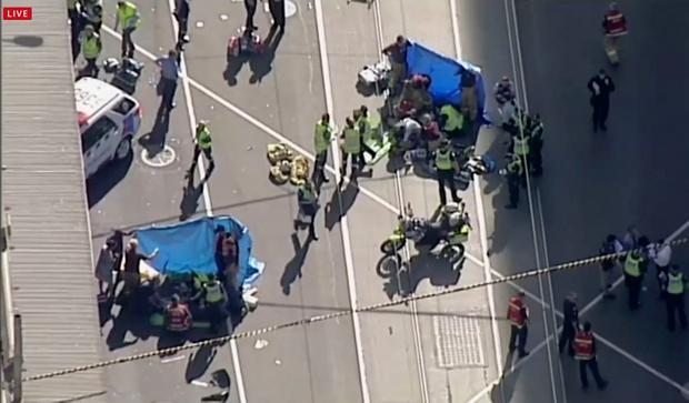 Emergency medical workers offer aid to victims struck by a vehicle, Thursday, Dec. 21, 20217, in Melbourne, Australia. Local media say over a dozen people have been injured after a car drove into pedestrians on a sidewalk in central Melbourne.