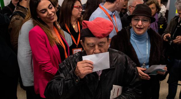 A voter wearing a traditional Catalan hat known as a barretina kisses his ballot before casting it yesterday