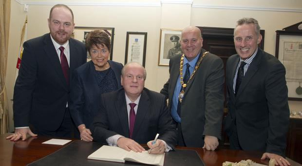 Former Ballymena Guardian editor Jim Flanagan signs the visitors' book in the mayor's parlour yesterday. Alongside him is his son James, wife Colette, mayor of Mid and East Antrim Borough Council Paul Reid and DUP MP Ian Paisley