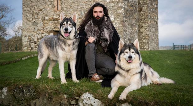 William Mulhall of Direwolf Tours in front of Audley's Castle, in Co Down, with Thor (left) and Odin, two Northern Inuit dogs he owns which played 'direwolves' in the hit HBO fantasy drama, Game Of Thrones.