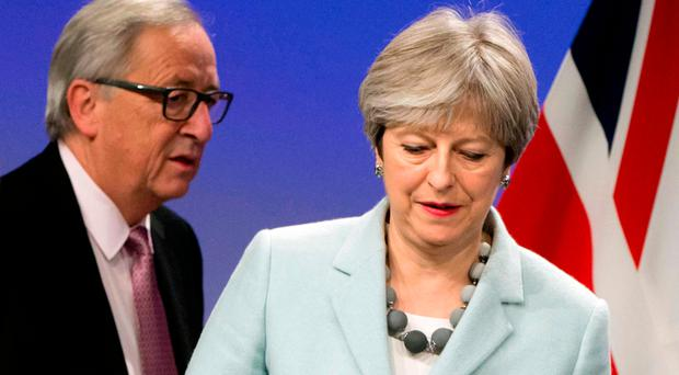 Theresa May, right, and European Commission President Jean-Claude Juncker prepare to address a media conference in Brussels after crisis talks over the Irish border