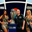 Rob Cross celebrates with the trophy after winning the final during day fifteen of the William Hill World Darts Championship at Alexandra Palace, London. Steven Paston/PA Wire.