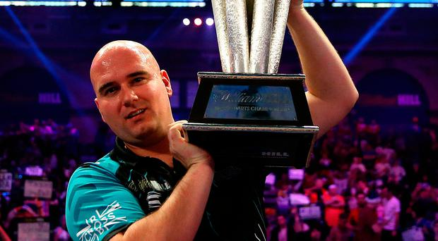 Rookie champion: Rob Cross lifts the world  championship trophy at his first attempt after beating Phil Taylor in his farewell game