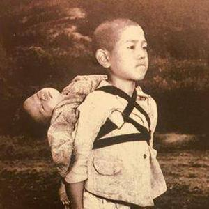 A boy carries his dead brother on his shoulders while he waits at a cemetery in Nagasaki in an image taken by US Marine Joe O'Donnell in 1945 Vatican Press Office