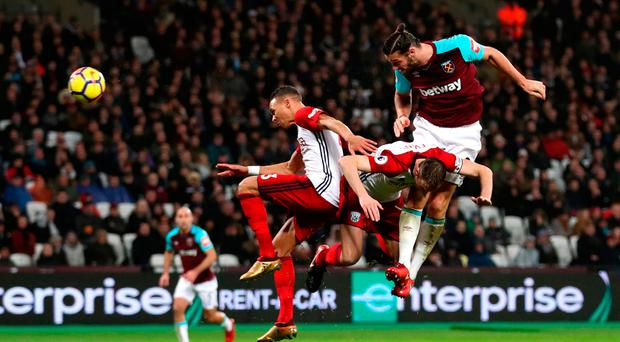 Powerful: Andy Carroll heads home