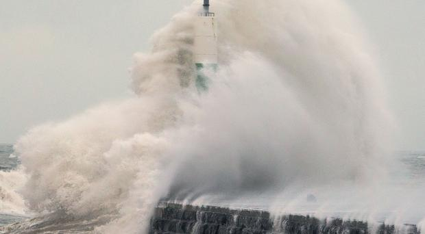 Waves crash over the stone jetty wall in Aberystwyth (Aaron Chown/PA)