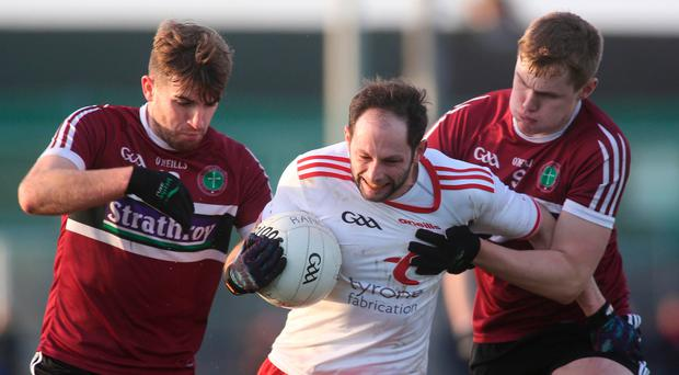 Tussle for ball: Tyrone's Ronan McNabb fights off St. Mary's duo Stephen McConville and Oisin O'Neill as the Reds Hands continue their bid for a seventh consecutive title