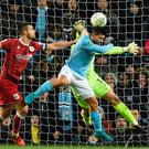 Manchester City's Argentinian striker Sergio Aguero (C) jumps to score their late winning goal during the English League Cup semi-final first leg football match between Manchester City and Bristol City.
