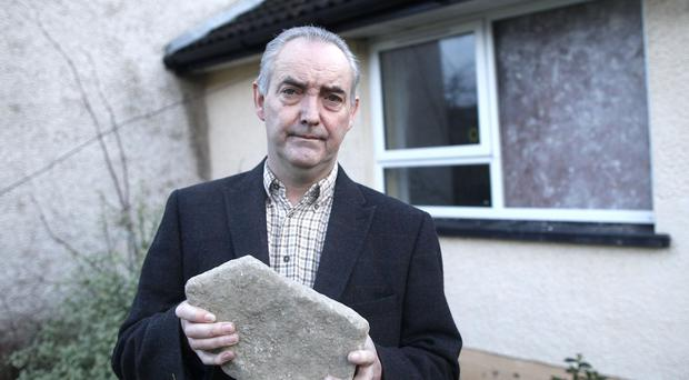 John McCabe holds the rock that was thrown through his window before Christmas