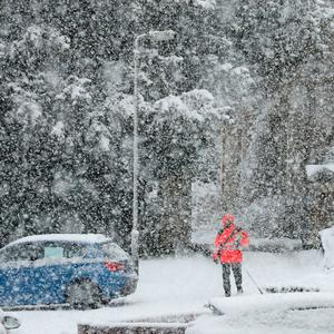 A postman delivers mail in snowy conditions. Pic: Andrew Milligan/PA Wire