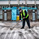 Playing sweeper: Ulster Council officer Liam Doherty helps clear snow at Healy Park, Omagh