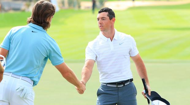 Rory McIlroy shakes the hand of clubhouse leader Tommy Fleetwood after the pair finished their pening rounds in Abu Dhabi.