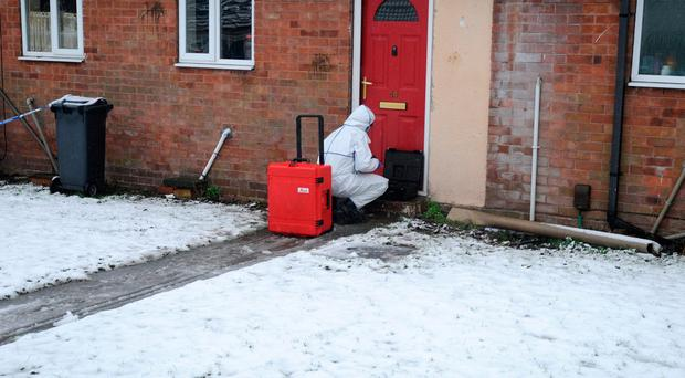 A police forensics officer works outside a property in Brownhills, near Walsall, where a child was discovered seriously wounded on Saturday night and died a short time later in hospital. Matthew Cooper/PA Wire