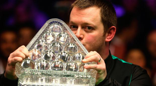 Mark Allen kisses the trophy as he celebrates victory in the Dafabet Masters