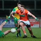 Dancing feet: Armagh's Eamon McGeown skips past Donegal's Caolan Ward and Caolain McGonigle