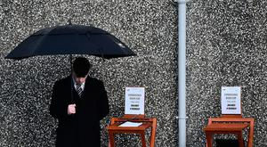 An undertaker stands beside a book of condolence outside St Ailbe's parish church in Ballybricken at Dolores O'Riordan's funeral on January 23, 2018 in Limerick, Ireland.