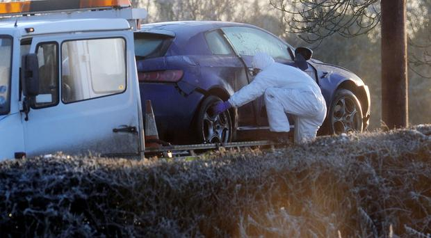 Forensics officers remove the Alfa Romeo in which PSNI officer Peadar Heffron was injured in a car bomb at Milltown Road in Co Antrim in 2010