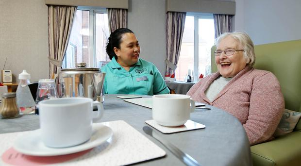 Care assistant Marife Elrequez chatting to resident of the Landsdowne Intermediate Care unit Jean Gourley