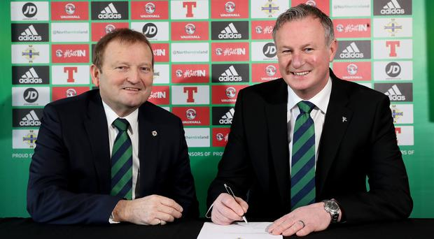 Michael O'Neill signs the four-year contract extension, which will see him continue as Northern Ireland senior men's international manager until 2024, as Irish FA President David Martin looks on.